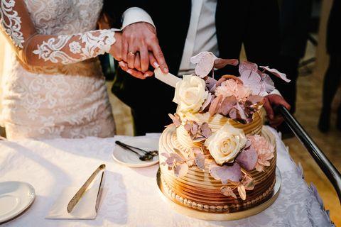 Hochzeitstorten-Deko: Ideen und Trends: Brautpaar schneidet mit Blumen geschmückte Torte an