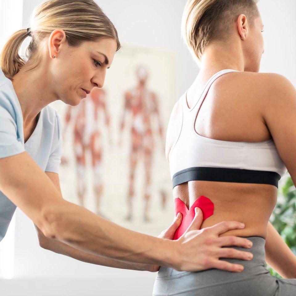 Physiotherapeut Gehalt: Physiotherapeutin knetet Frau am unteren Rücken