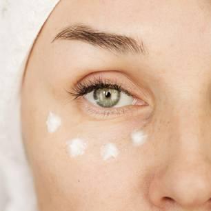 Falten unter den Augen: Frau mit Creme unter dem Auge