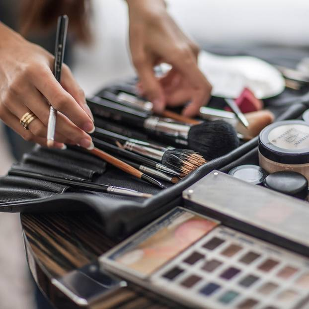 Make-up auffrischen: Make-up-Artist mit Pinseln in der Hand
