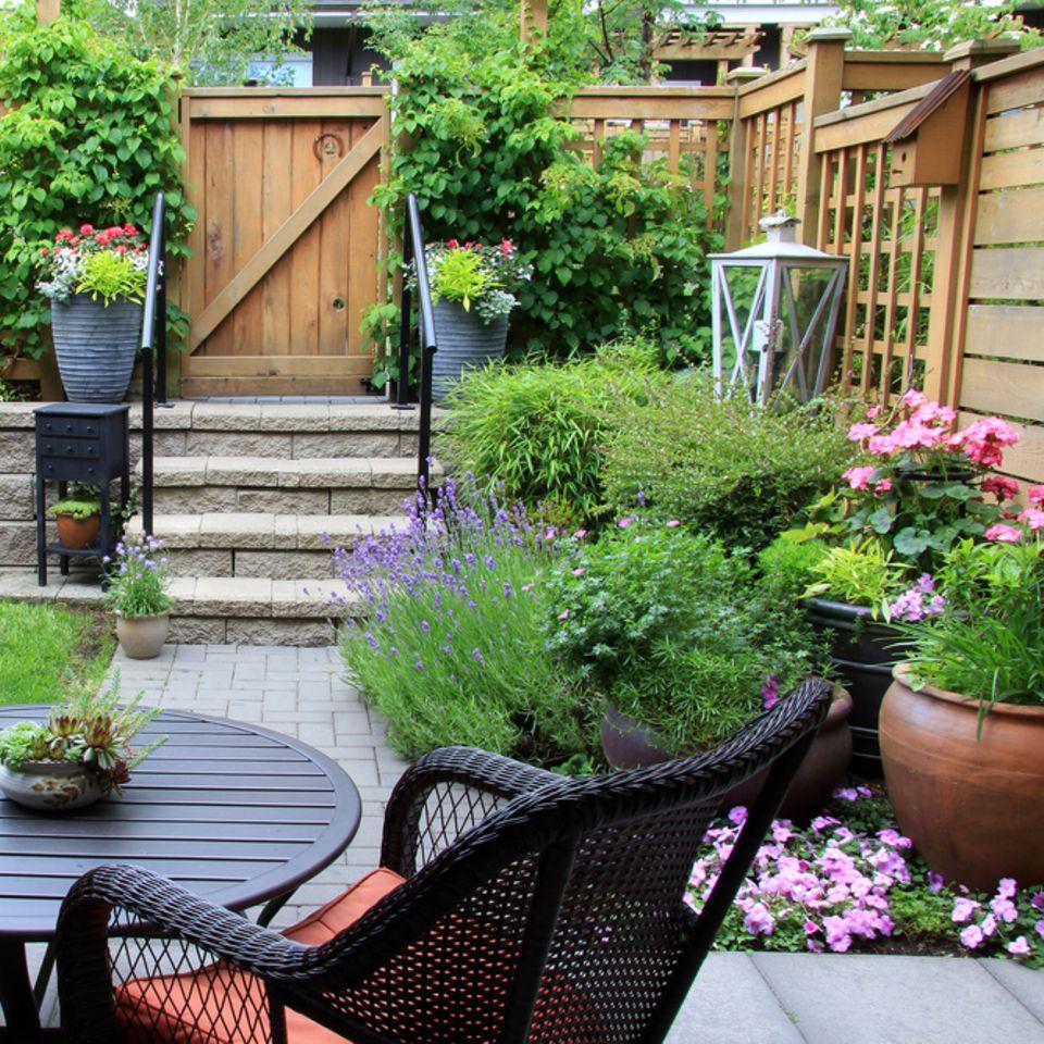 Kleiner Garten: So gestaltest du ihn richtig! Garten mit Stühlen, Tisch und Blumen links und rechts