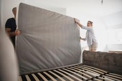 Matratze entsorgen: Mann und Frau nehmen Matratze vom Bett