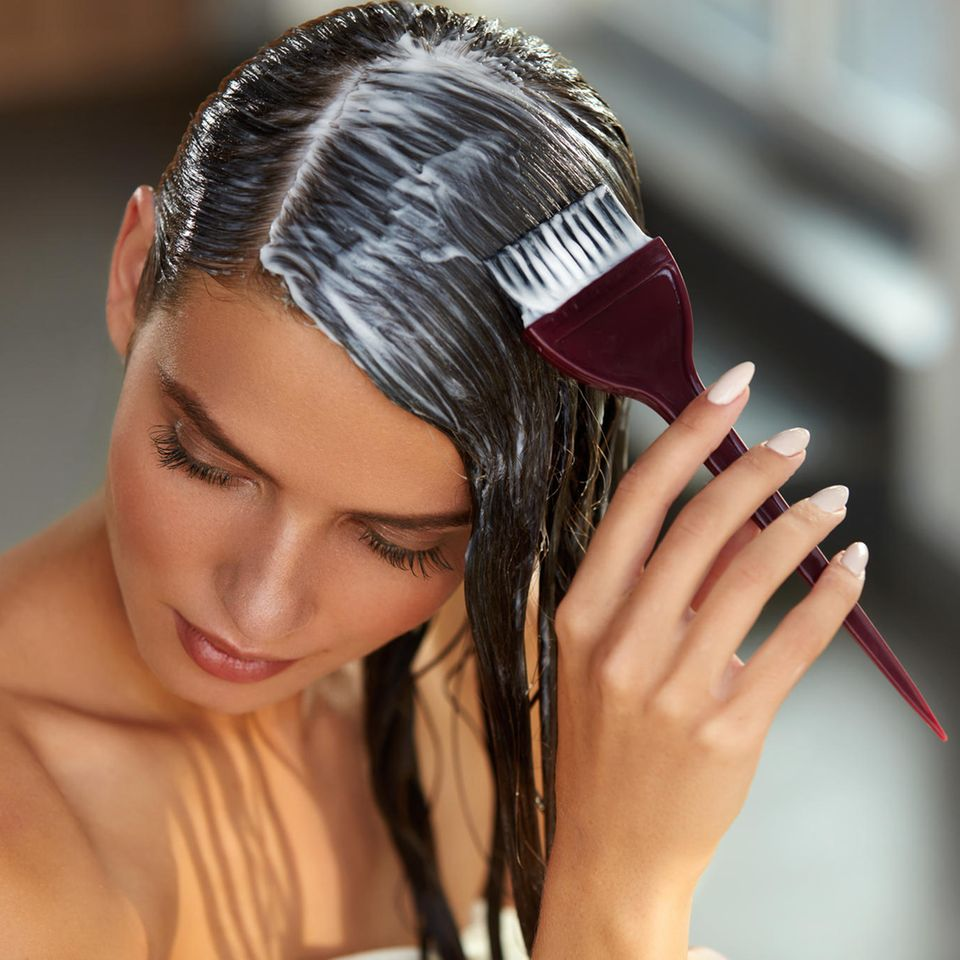 Haare tönen: Frau trägt Tönung mit einem Pinsel auf die Haare auf