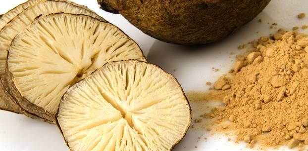 Pueraria mirifica: Was ist dran an der Heilpflanze? In dicke Scheiben geschnittene Pueraria mirifica, daneben Pulver