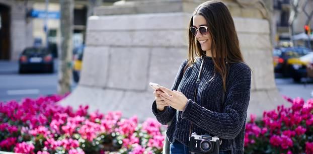Trendteile für den Frühling: Frau mit Kamera und Smartphone