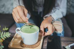 Matcha-Tee: Frau rührt in Matcha-Tee