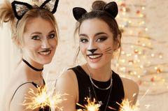 Als Katze schminken: Zwei Frauen im Katzen-Look und Wunderkerzen