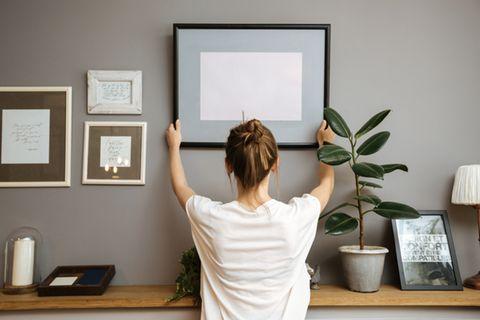 Bilder aufhängen: So geht's richtig: Frau hängt Bilderrahmen an Wand auf