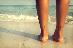 Kleine Tattoos: Eine Frau mit zwei kleinen Tattoos an der Rückseite der Unterschenkel