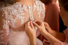Trauzeugen Aufgaben: Checkliste und Tipps für dich! Trauzeugin knöpft Brautkleid zu