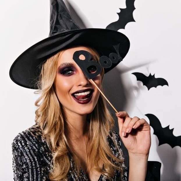 Hexe schminken: Frau mit Hexenhut und Halloween-Deko