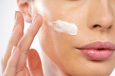 SOS-Tipps für zickige Haut: Frau cremt sich das Gesicht ein