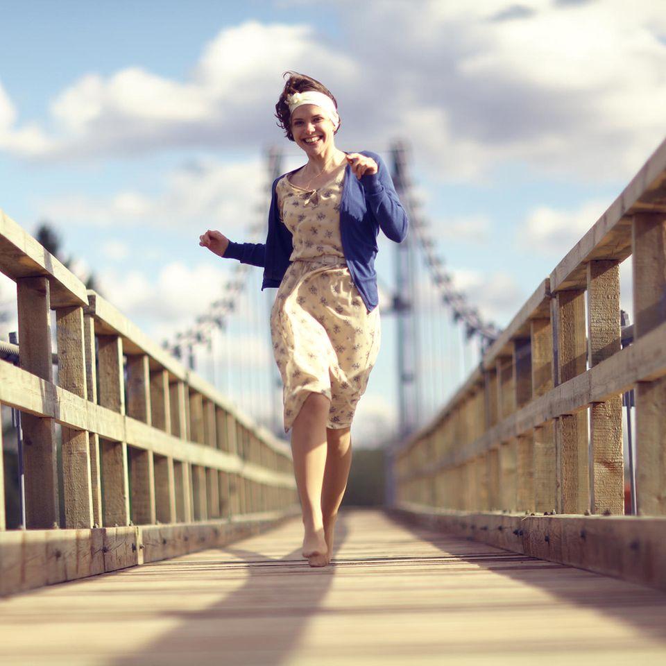 Mit diesem Glücks-Trick gehst du fröhlicher durchs Leben: Eine Frau geht tänzelnd über eine Brücke