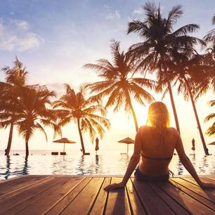 Unbezahlter Urlaub: Frau entspannt am Pool unter Palmen
