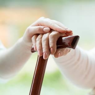 Mehr Geld für soziale Berufe: Pflegerin hält die Hand einer alten Frau