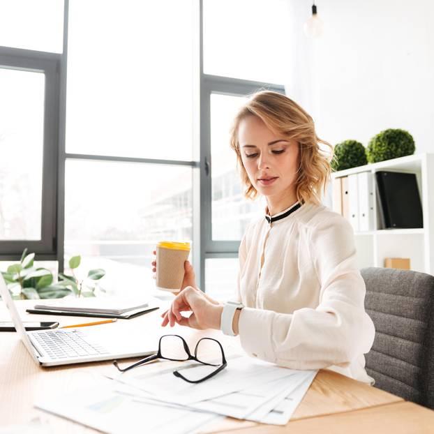 Schluss mit dem Teilzeit-Tabu: Frau am Schreibtisch, schaut auf die Uhr