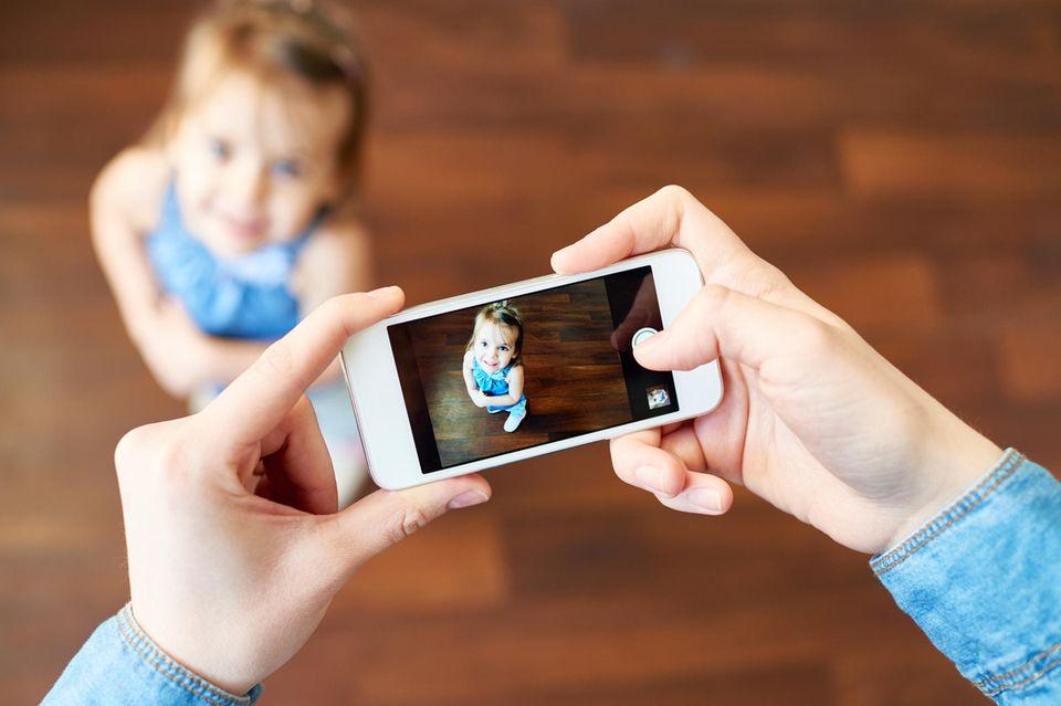 Kind wird mit Smartphone fotografiert