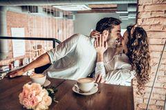 Was erwarten selbstbewusste Frauen in der Beziehung: Eine selbstbewusste Frau zieht ihren Mann zu sich rüber und küsst ihn