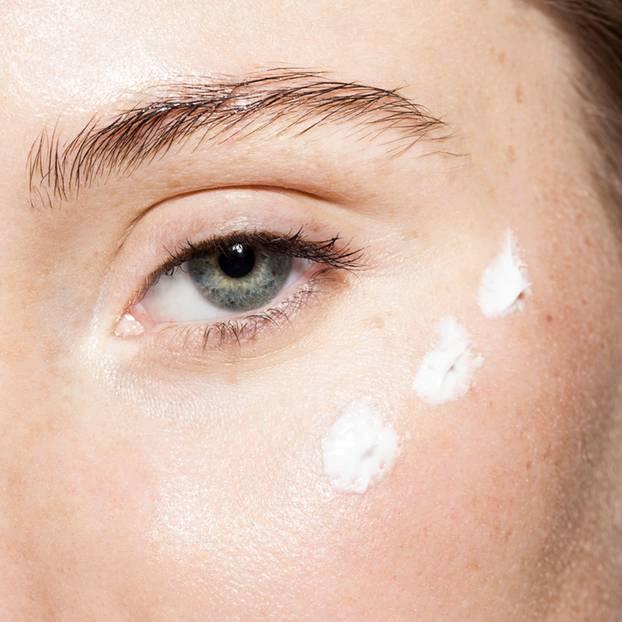 Augenpflege falsch auftragen: Frau mit Creme unter dem Auge