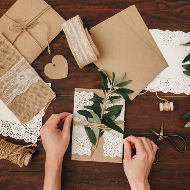 Hochzeitseinladungen selber machen - die schönsten Ideen: Frau bindet Zweig mit Sisalbändchen um eine Karte
