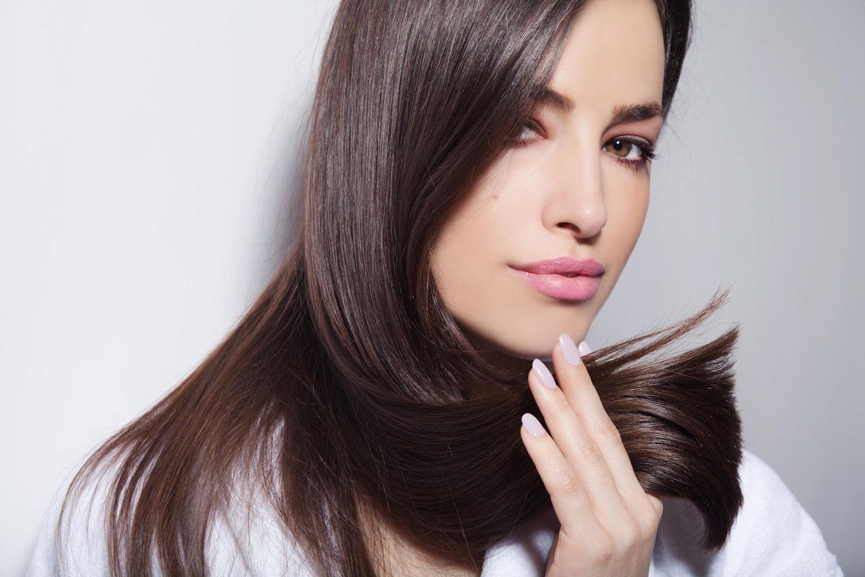 Wie schnell wachsen Haare: Frau mit braunen Haaren und einer Haarsträhne in der Hand