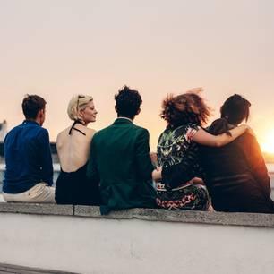 Gemeinsamer Freundeskreis: 5 Menschen beobachten Sonnenuntergang