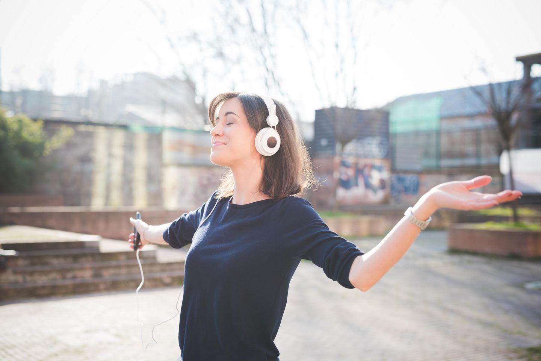 Kraftquellen der Redaktion: Eine Frau tanzt mit Kopfhörern auf den Ohren