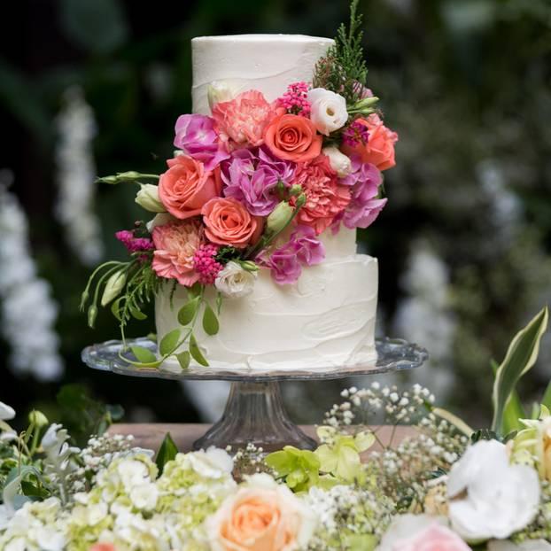 Rosenhochzeit: Bedeutung, Geschenke und Outfits: Helle dreistöckige Hochzeitstorte mit Rosen geschmückt