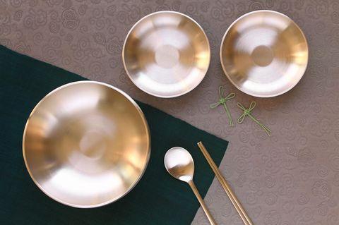 Messing reinigen: 5 wirksame Hausmittel: Drei Messingschalen und Besteck auf einem Tisch