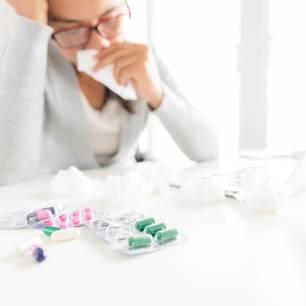 Krank in der Probezeit: Das solltest du wissen: Frau sitzt mit Taschentüchern und Medikamenten am Schreibtisch