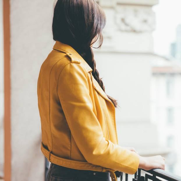 Welche Probleme haben glückliche Menschen? Eine Frau in gelber Jacke auf einem Balkon