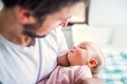 Elternzeit als Vater: Mann hält Baby im Arm