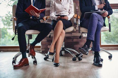 Allein unter Männern: Frau sitzt zwischen zwei Männern