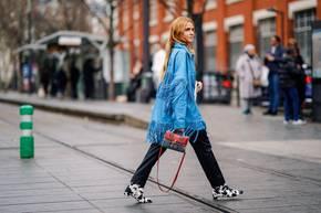 Cow Prints: Frau mit blauer Fransen-Jacke und Kuh-Print-Stiefeletten