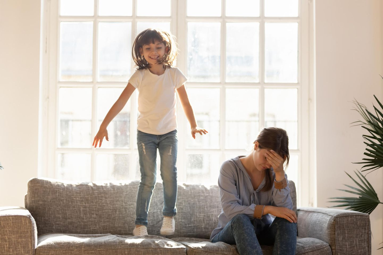 Patchwork-Mama gesteht: Ein Kind hüpft auf dem Sofa, während eine Frau genervt zu Boden schaut