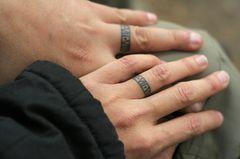 Partner Tattoo: Ein Paar mit tätowierten Ringen auf den Fingern