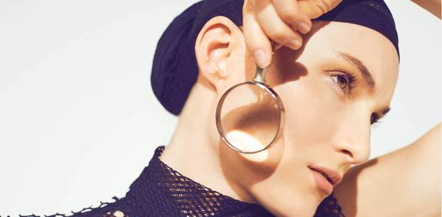 Perfekte Haut: Frau hält sich Lupe ans Gesicht
