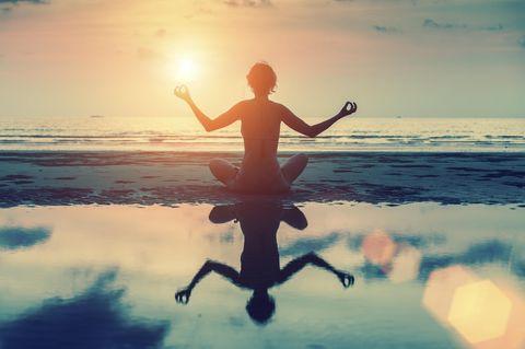 Mantras für Selbstbewusstsein: Frau meditiert am Wasser