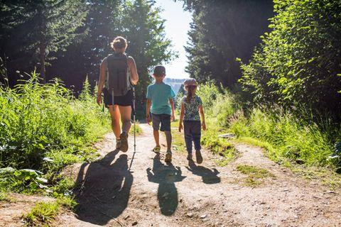 Wandern mit Kindern: Tipps und Touren: Frau wandert mit zwei Kindern an ihrer Seite
