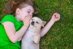 Haustiere für Kinder: Mädchen liegt mit Chihuahua auf dem Rasen und flüstert dem Hund etwas ins Ohr
