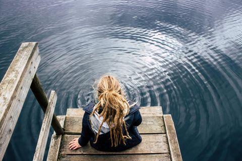 Selbstzweifel: Eine junge Frau sitzt grübelnd am See