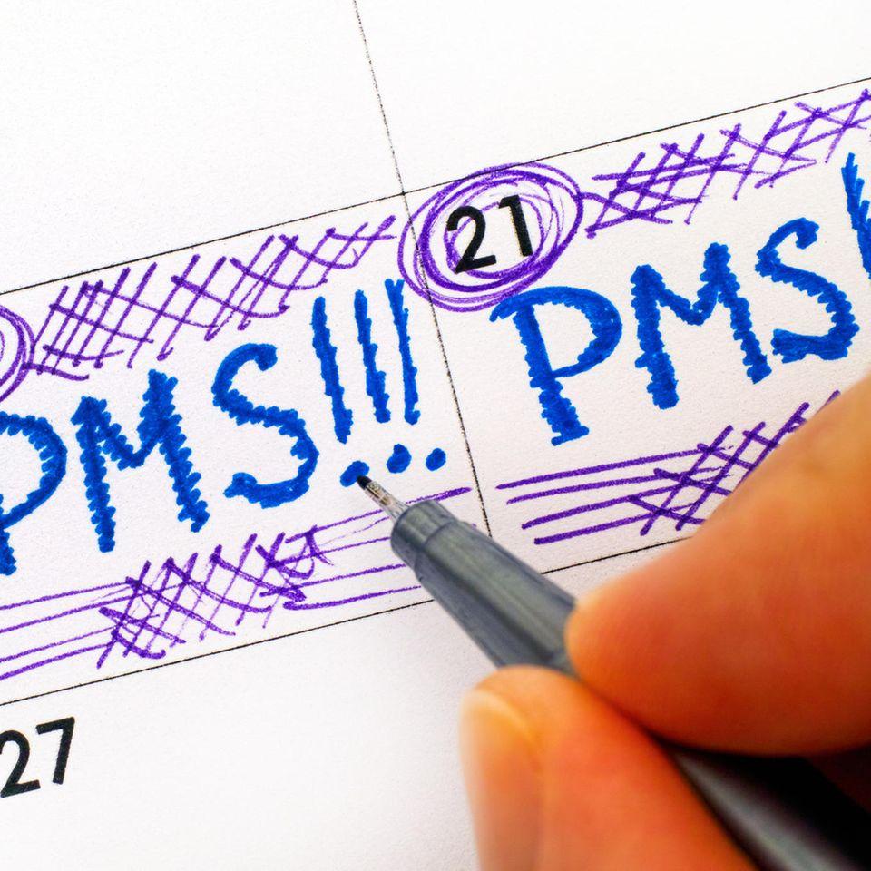 PMS: Frau trägt PMS in den Kalender ein