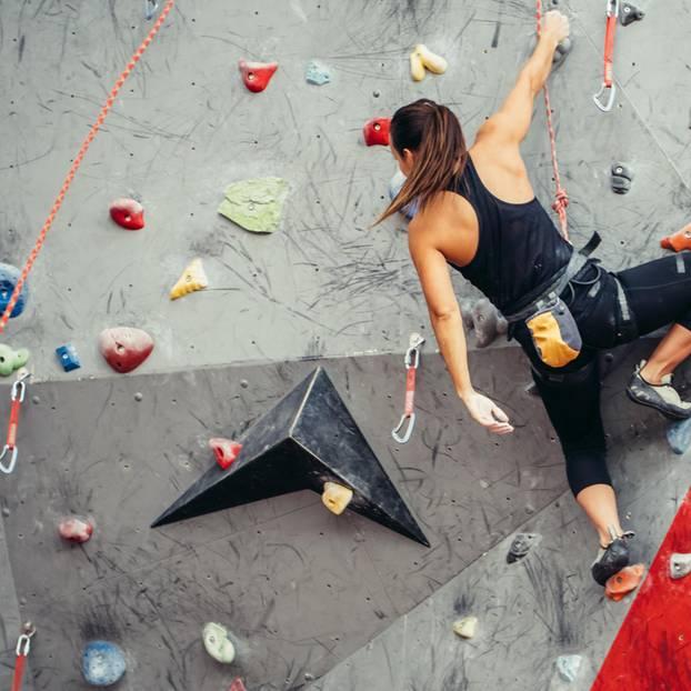 Hobbys im Lebenslauf? Frau klettert Wand hoch
