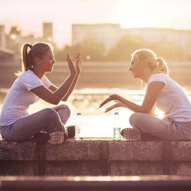 So bereichern Krebse unser Leben: Zwei Frauen sitzen auf einer Mauer vor einem großen Gewässer