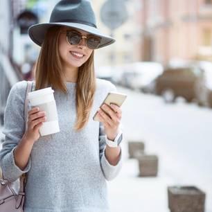 Blau machen: Frau spaziert mit Getränk und Handy