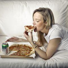Gewohnheiten erfolgreicher Frauen: Eine Frau liegt auf dem Sofa und isst Pizza