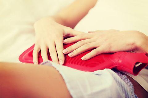 Hausmittel gegen Bauchschmerzen: Frau mit einer Wärmflasche
