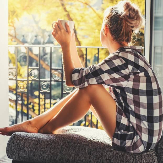 Was man als Single alles lernen kann: Eine junge Single-Frau schaut aus dem Fenster