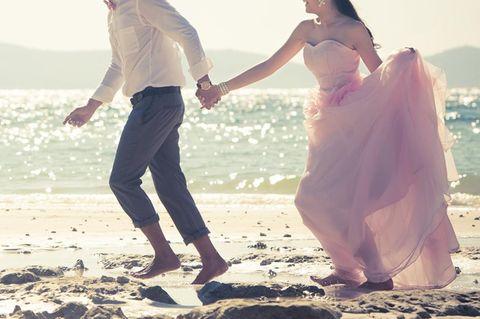 Freie Trauung: Braut und Bräutigam rennen am Strand entlang