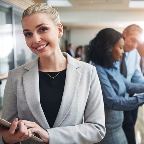 Betriebsrat gründen: Das solltest du wissen: Frau auf der Arbeit lächelt in die Kamera, hinter ihr stehen Kollegen